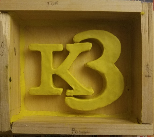 clay logo in wooden form frame